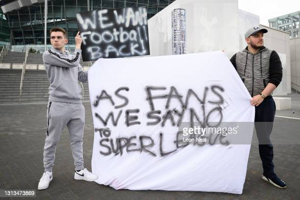 Manchester United fan Jack Newson and Tottenham Hotspur fan Cameron Bull hold their handmade signs as they protest against the proposed Super League...