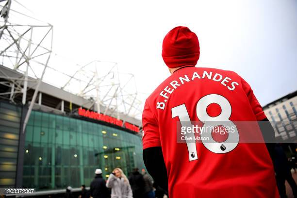 Manchester United fan looks on outside the stadium while wearing a shirt with new signing Bruno Fernandes name and number prior to the Premier League...