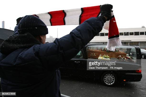 A Manchester United fan pays tribute as the funeral cortege of Busby Babe Albert Scanlon passes Old Trafford in Manchester
