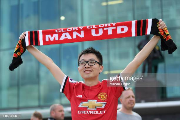 Manchester United fan pose for a photo ahead of the Premier League match between Manchester United and Chelsea FC at Old Trafford on August 11 2019...