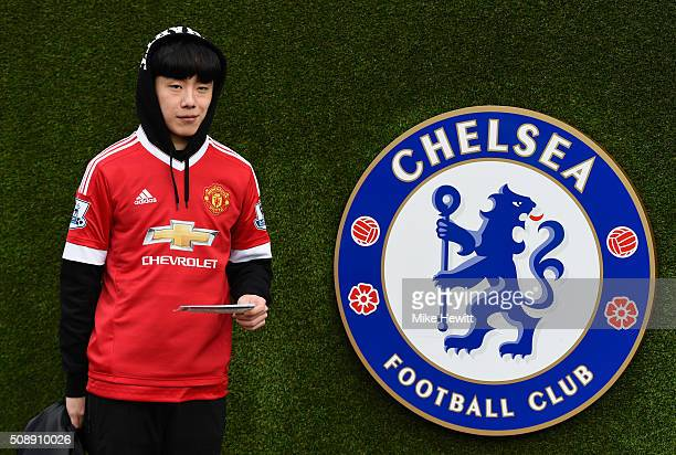 Manchester United fan poses next to the Chelsea club crest prior to the Barclays Premier League match between Chelsea and Manchester United at...
