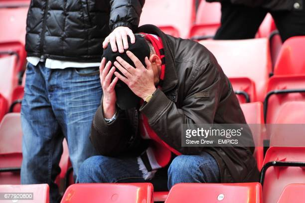 A Manchester United fan sits dejected in the stands