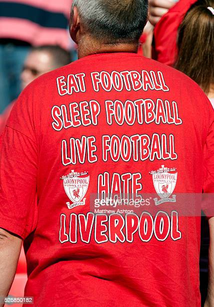A Manchester United fan wearing a tshirt showing the rivalry with Liverpool