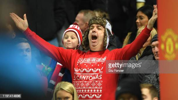 Manchester United fan with an Eric Cantona festive jumper sings during the Premier League match between Manchester United and Aston Villa at Old...
