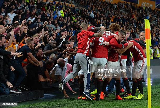 Manchester United fans break an advertising hoarding as they celebrate Marcus Rashford's last minute winner with the Manchester United team during...