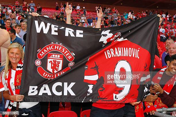Manchester United fans celebrate after Manchester United beat Leicester City to win the FA Community Shield football match at Wembley Stadium in...