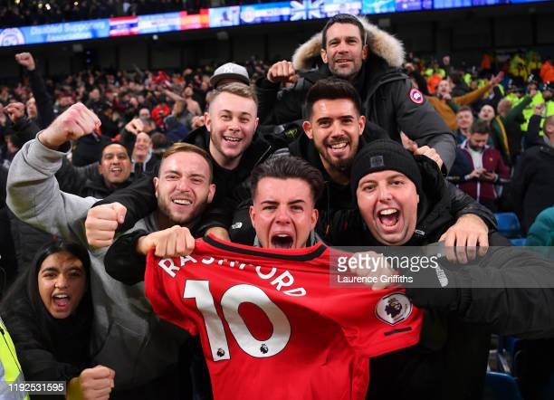 Manchester United fans celebrate with Marcus Rashford of Manchester United's shirt following the Premier League match between Manchester City and...