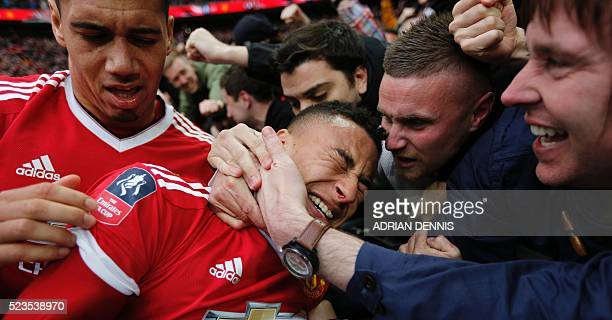 Manchester United fans congratulate Manchester United's English midfielder Jesse Lingard as they celebrate with the crowd after Manchester United's...