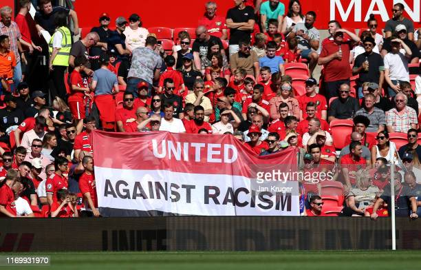 Manchester United fans display an antiracism banner prior to the Premier League match between Manchester United and Crystal Palace at Old Trafford on...