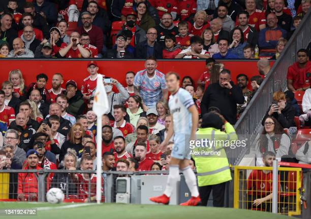 Manchester United fans gesture towards Mark Noble of West Ham United as he takes a corner during the Carabao Cup Third Round match between Manchester...