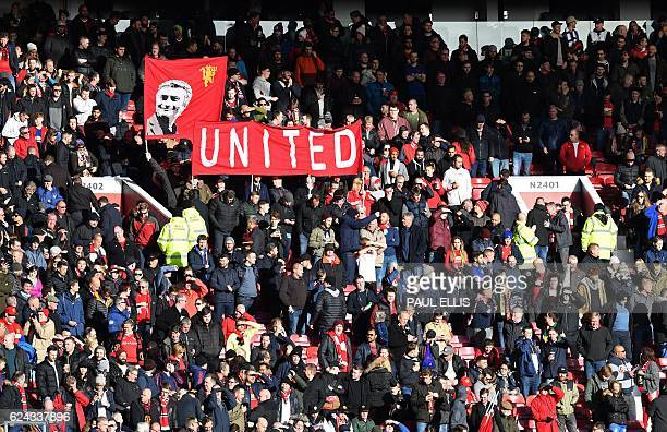 Manchester United fans hold a banner depicting Manchester United's Portuguese manager Jose Mourinho ahead of the English Premier League football...
