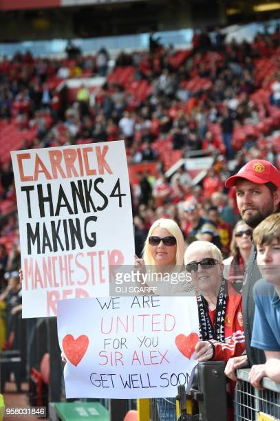 Manchester United fans hold a banner wishing former manager Alex Ferguson who is convalescing after having emergency surgery on a brain haemorrhage...