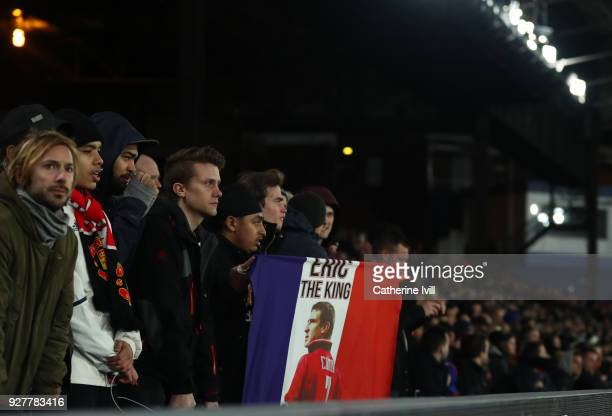 Manchester United fans hold up a French flag with a picture of Eric Catona on it during the Premier League match between Crystal Palace and...