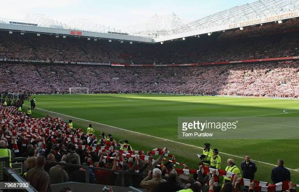 Manchester United fans hold up scarves in memory of the 23 victims of the Munich Air Disaster ahead of the Barclays FA Premier League match between...