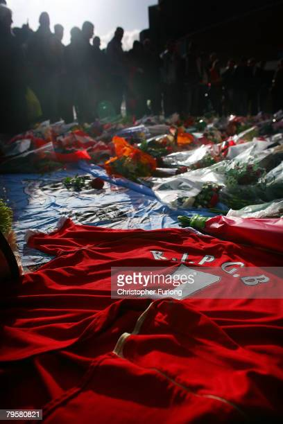Manchester United fans look at floral tributes laid beside football shirts during a minute's silence at Old Trafford on February 6 2008 in Manchester...