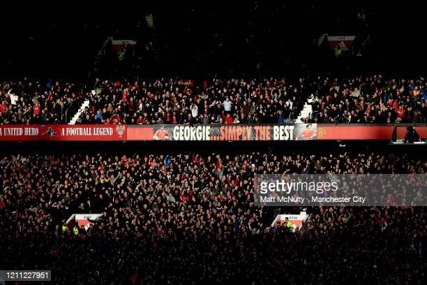 Manchester United fans look on during a sunset during the Premier League match between Manchester United and Manchester City at Old Trafford on March...