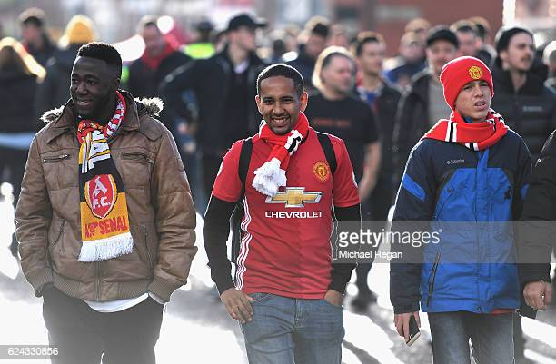 Manchester United fans make their way to the stadium prior to kick off during the Premier League match between Manchester United and Arsenal at Old...