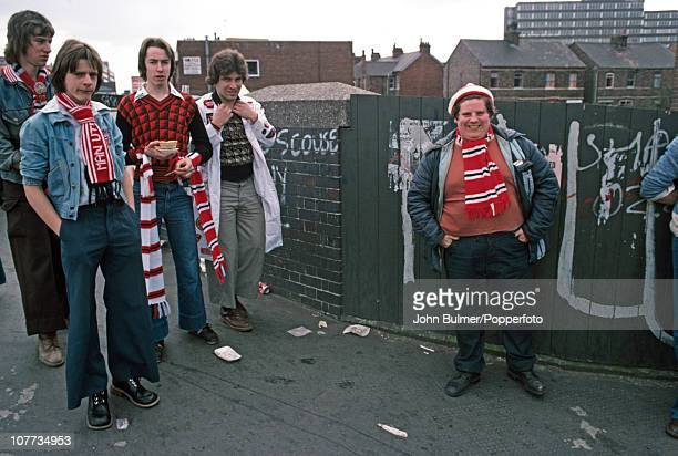 Manchester United fans one holding a pie congregate in Manchester prior to a home game in 1976
