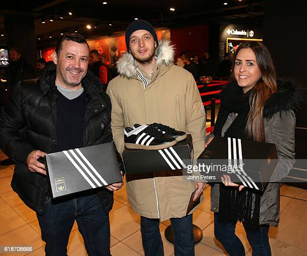 Manchester United fans pose inside the club Megastore after the launch of the new adidas Ashington shoe named in honour of Sir Bobby Charlton's 60...