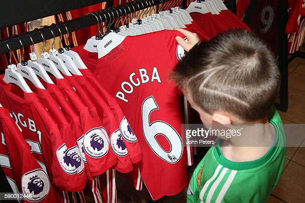 Manchester United fans shop for 201617 home kit with Paul Pogba's name and number on the back at the Manchester United Megastore at Old Trafford on...