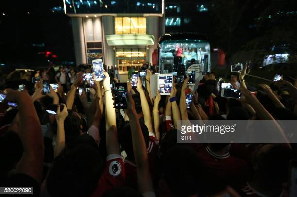 TOPSHOT Manchester United fans take photos as team members board a bus for the airport after the cancelation of the match between Manchester United...
