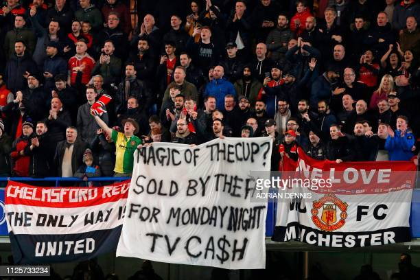 Manchester United fans unfurl a banner protesting against the fixture scheduling during the English FA Cup fifth round football match between Chelsea...
