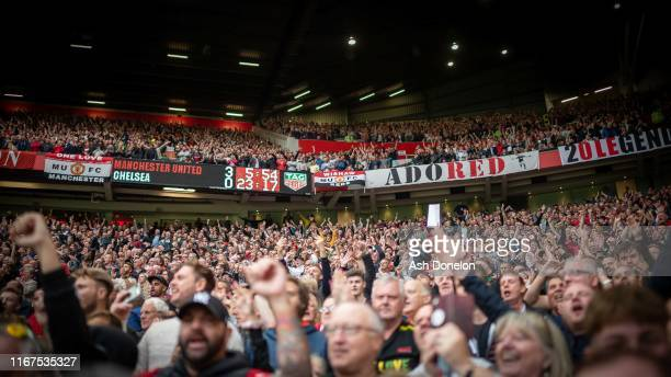 Manchester United fans watch from the stand during the Premier League match between Manchester United and Chelsea FC at Old Trafford on August 11...