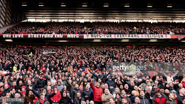 Manchester United fans watch from the stand during the Premier League match between Manchester United and Manchester City at Old Trafford on March 08...
