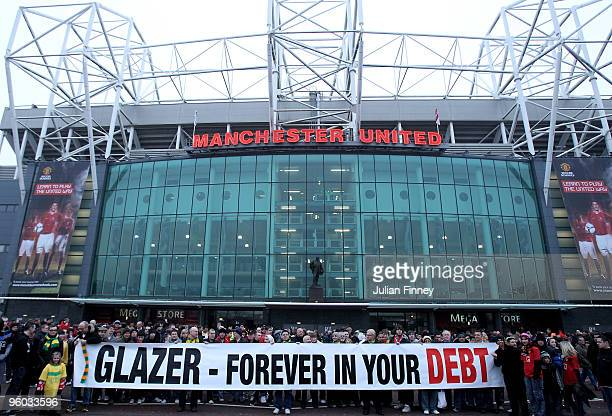 Manchester United fans wearing green and gold scarves protest against the Glazers current owners of Manchester United before the Barclays Premier...