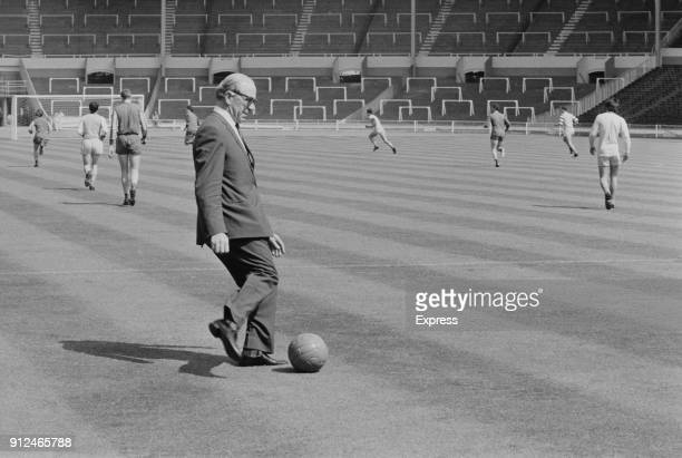 Manchester United FC manager Matt Busby about to kick a soccer ball during training ahead of the European Cup Final at Wembley Stadium, London, UK,...