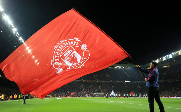 Manchester united v liverpool uefa europa league round of a manchester united flag being waved on the touchline voltagebd Image collections