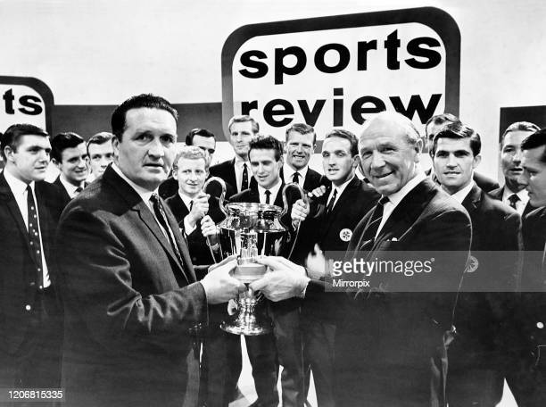 Manchester United football manager Matt Busby handing the Team of the Year Trophy to Celtic manager Jock Stein, while the rest of the Celtic team...