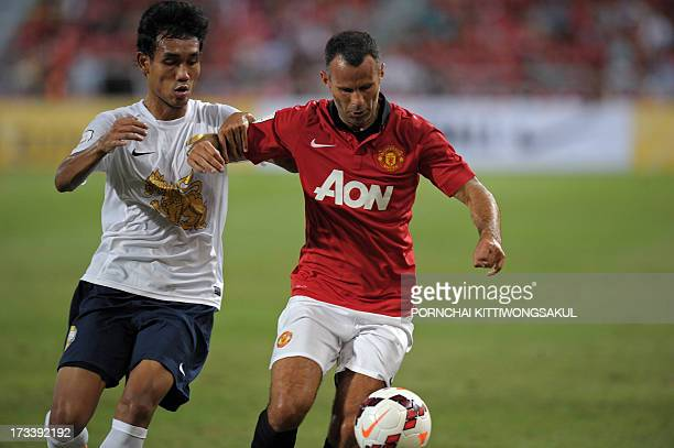 Manchester United football player Ryan Giggs battles for the ball with Teerasil Dangda of the Singha All Star during an exhibition match at...