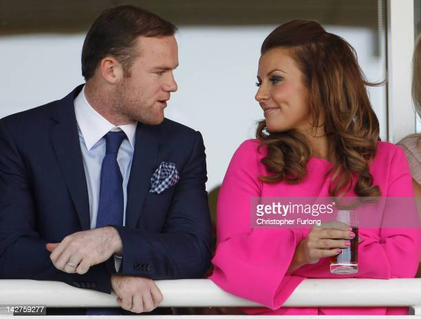 Manchester United football player Wayne Rooney and his wife Coleen watch the racing during the first day of the Aintree Grand National meeting on...