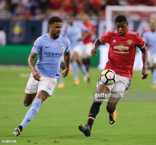 Manchester United forward Marcus Rashford brings the ball up the pitch as Kyle Walker of Manchester City defends in the first half at NRG Stadium on...