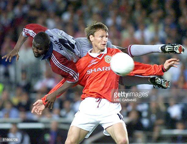 Manchester United forward Teddy Sheringham tries to kick the ball while Bayern Munich defender Samuel Osei Kuffour flies in the air 26 May 1999 at...