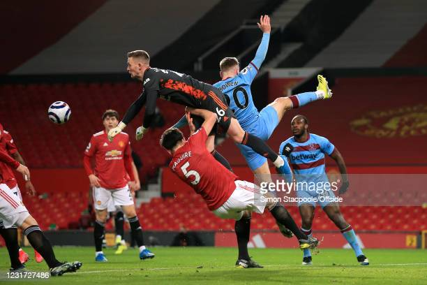 Manchester United goalkeeper Dean Henderson punches clear from Harry Maguire of Manchester United and Jarrod Bowen of West Ham United during the...