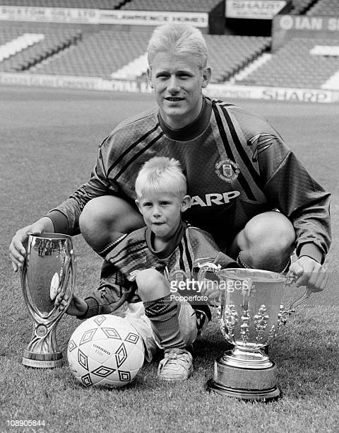 Manchester United goalkeeper Peter Schmeichel with son Kasper and the League Cup and UEFA Super Cup at Old Trafford Manchester in August 1992