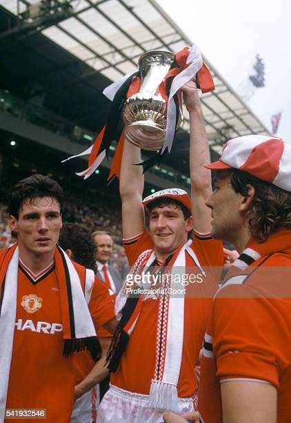 Manchester United goalscorer Norman Whiteside holding the trophy flanked by Frank Stapleton and Bryan Robson after the FA Cup Final between...