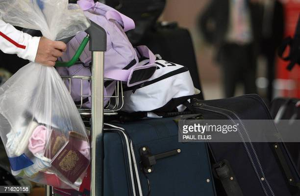 Manchester, UNITED KINGDOM: A passenger hold their personal belongings in plastic bags 10 August 2006 while waiting to check in at Manchester...