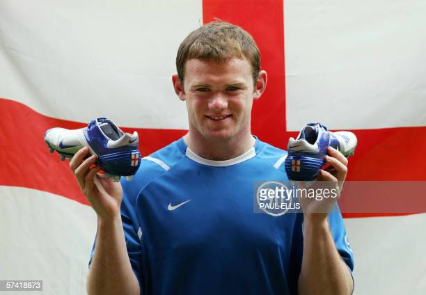 England and Manchester United soccer player Wayne Rooney holds the boots that he will wear during this summer's World Cup in Germany at photocall at...