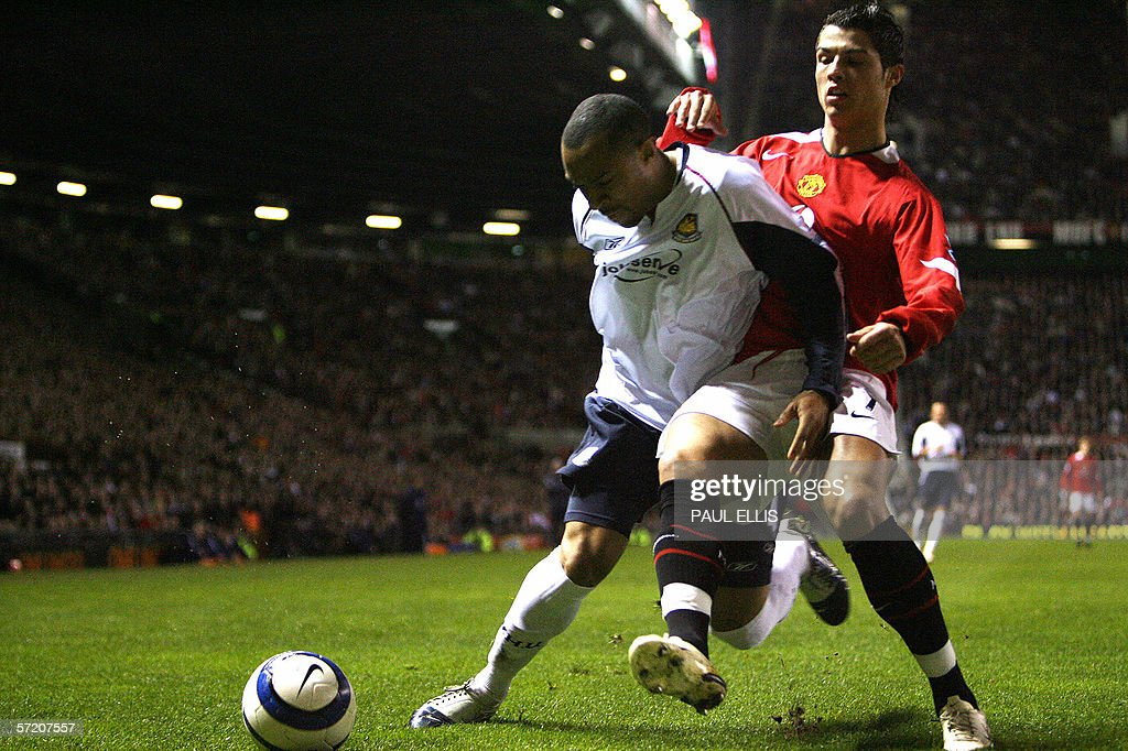 Manchester United's Cristiano Ronaldo (R) is held back by from West Ham United's Danny Gabbidon during their English Premiership soccer match at Old Trafford, Manchester, 29 March 29. AFP PHOTO/PAUL ELLIS Mobile and website use of domestic English football pictures subject to subscription of a license with Football Association Premier League (FAPL) tel : +44 207 298 1656. For newspapers where the football content of the printed and electronic versions are identical, no licence is necessary.