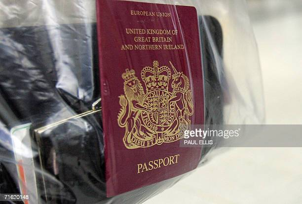 Manchester, UNITED KINGDOM: Passengers hold their personal belongings in plastic bags 10 August 2006 while waiting to check in at Manchester Airport,...