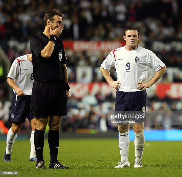 Referee Kim Milton Nielsen talks with England's Wayne Rooney during the game against Poland defence during the FIFA World Cup Group 6 qualifying...