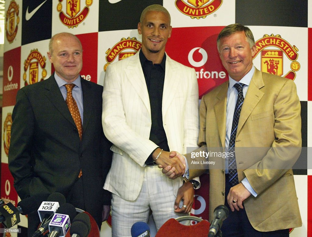 Manchester United manager, Alex Ferguson (R) and Chief Executive Peter Kenyon (L) show off new signing Rio Ferdinand at a press conference at Old Trafford, Manchester, England on July 22, 2002. Kenyon resigned as Chief Executive of Manchester United September 9, 2003 to take up a position with Chelsea.