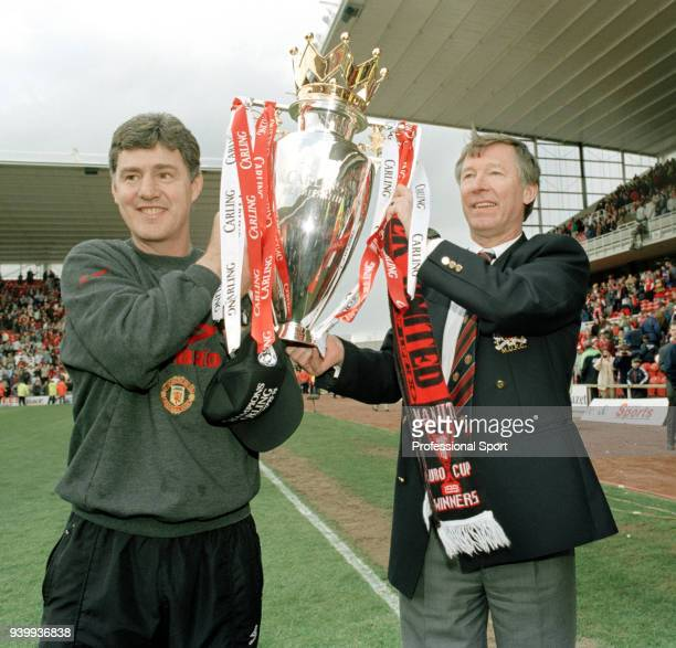 Manchester United manager Alex Ferguson and coach Brian Kidd celebrate with the trophy after being crowned FA Carling Premiership champions following...