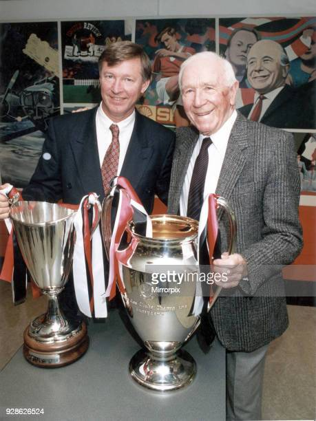 Manchester United manager Alex Ferguson and former manager Sir Matt Busby posing with the European trophies which they ech won as United manager...