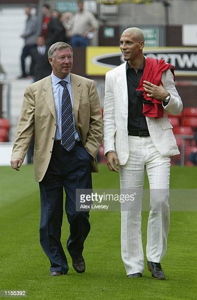 Manchester United manager Alex Ferguson takes a walk with new signing rio Ferdinand at a press conference at Old Trafford Manchester England on July...
