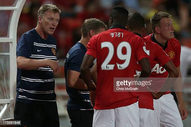 Manchester United manager David Moyes gives instructions Wilfried Zaha during the friendly match between Singha All Star XI and Manchester United at...