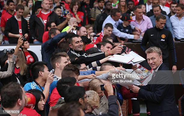 Manchester United manager David Moyes signs autographs before the Rio Ferdinand Testimonial Match between Manchester United and Sevilla at Old...